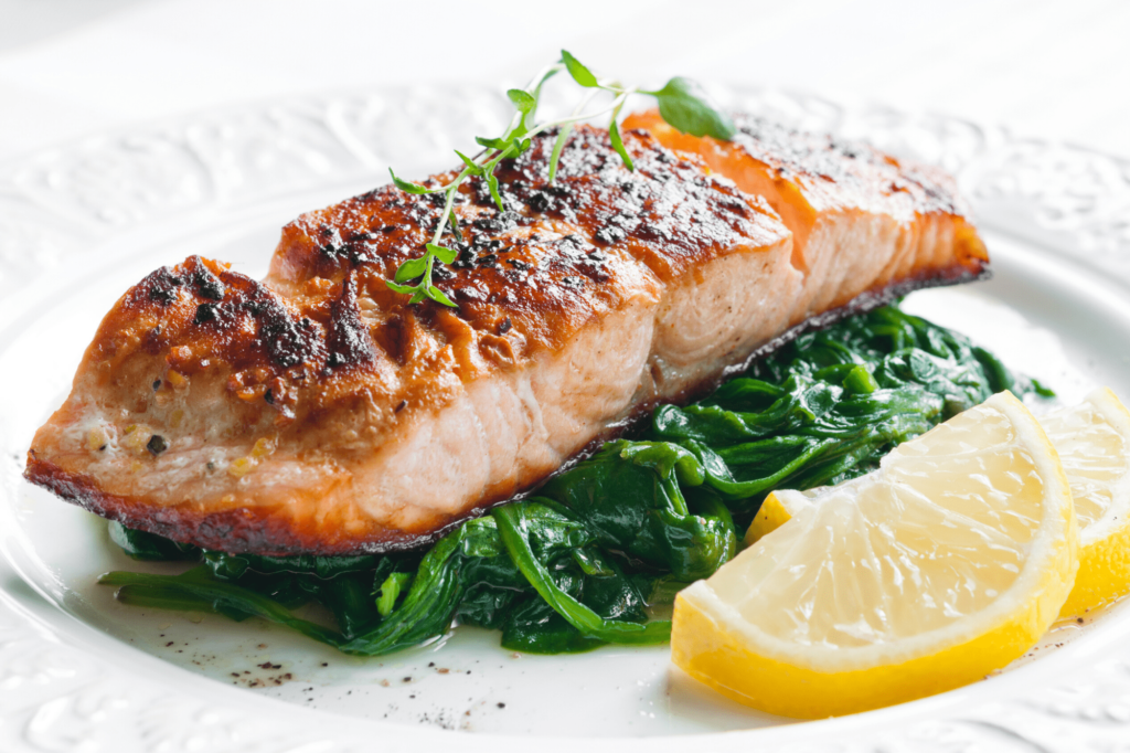 salmon and protein, one of the best foods for weight loss, on a bed of spinach