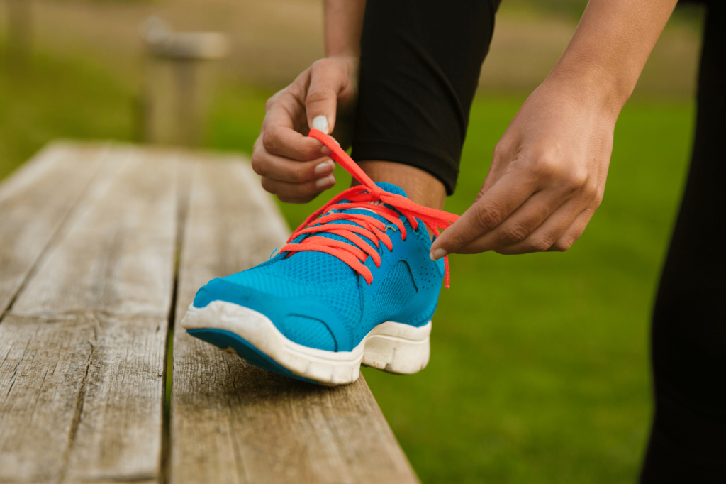 person tying red shoe lace on blue running shoe, foot on top of bench for permanent weight loss