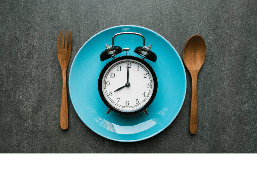 blur plate with clock in the middle, wooden fork on the left, wooden spoon on the right