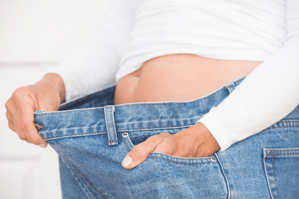 person showing weight loss on waist, jeans are too big