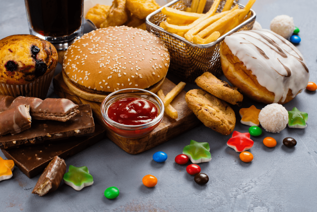 a collection of unhealthy foods for weight loss including hamburger, french fries, donut, candy, ketchup, chocolate and muffin