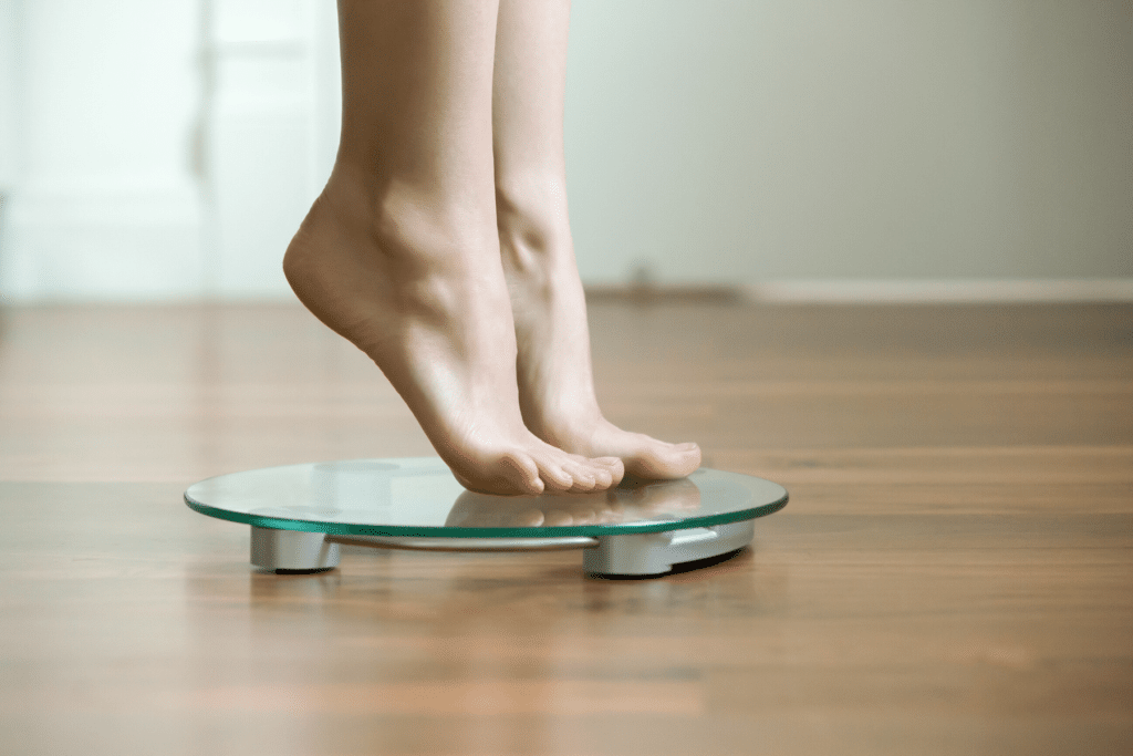 person gingerly stepping on scale to weigh yourself daily