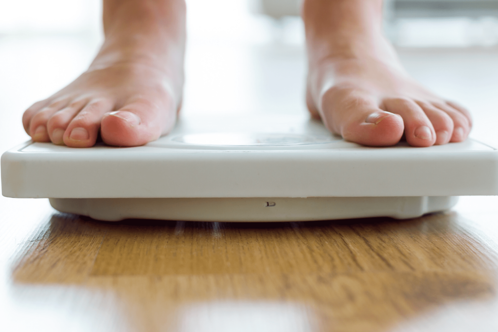 person standing on scale weighing themselves for permanent weight loss