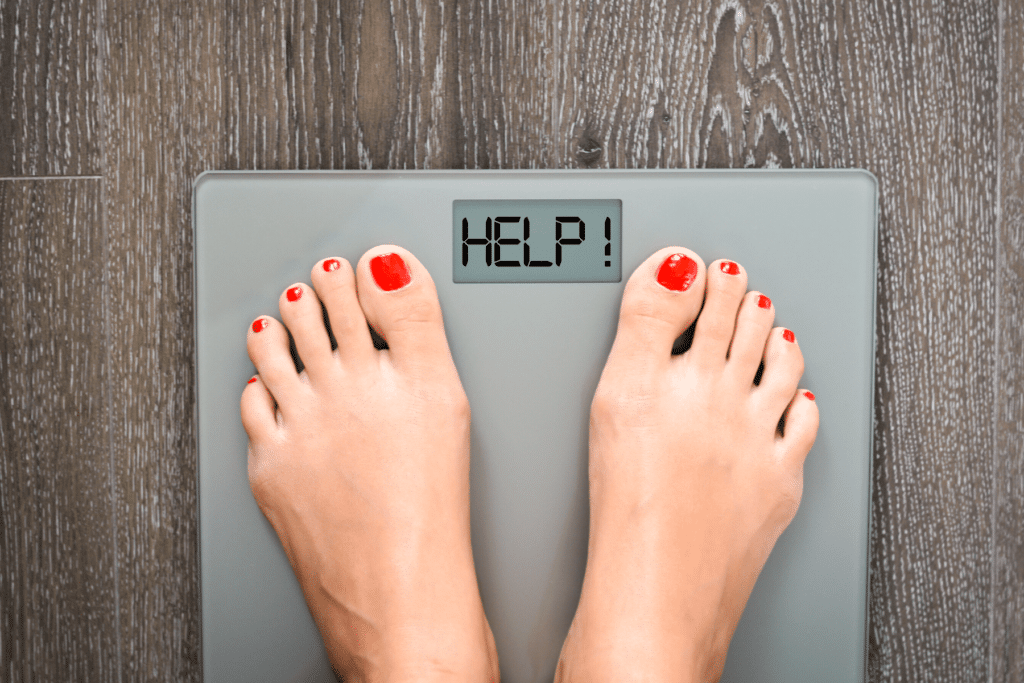 person on scale that says help instead of weight