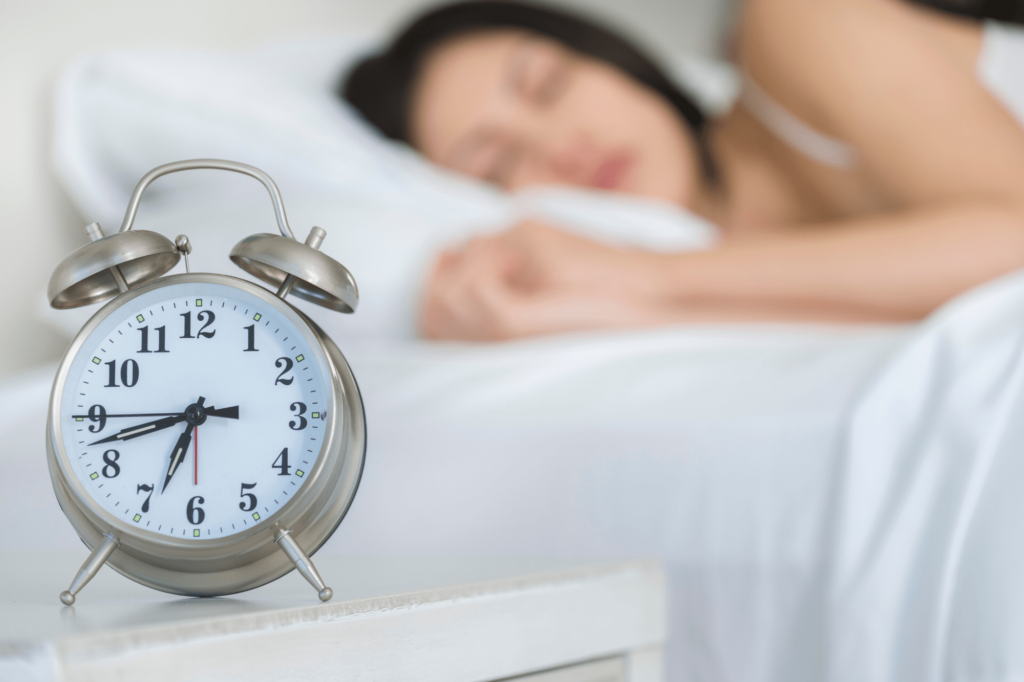 woman sleeping with alarm clock in the forefront