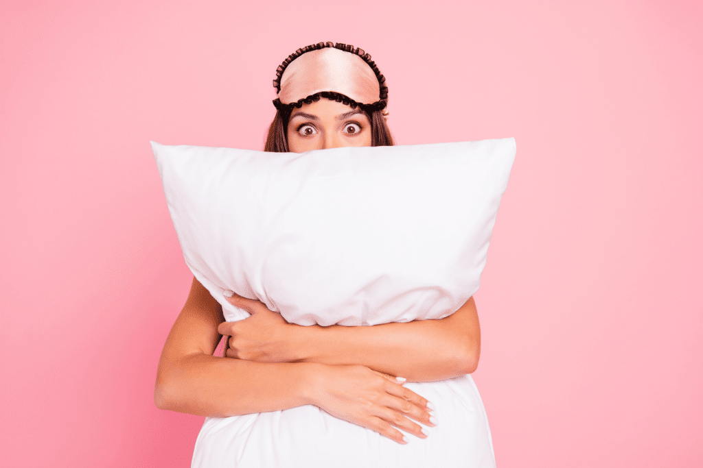 woman with eye mask holding a large pillow