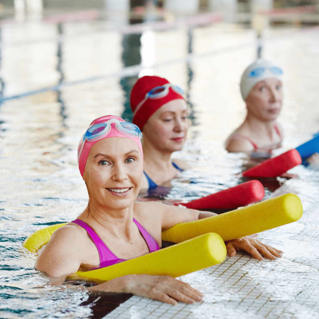 three smiling women in a pool holding pool noodles, swimming is a good option for overweight women