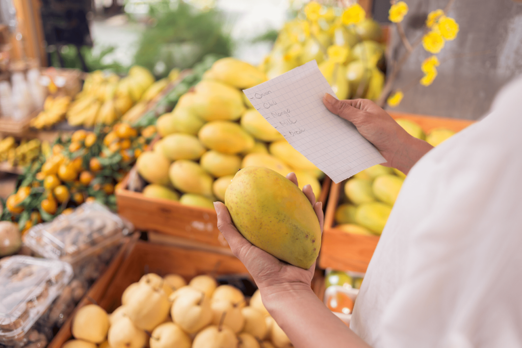 person in grocery store holding mango in one hand and shopping list in the other hand